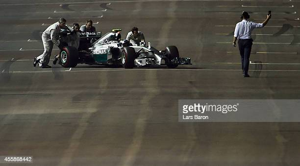 Nico Rosberg of Germany and Mercedes GP is pushed off the track by his team after experiencing problems during the start of the formation lap during...
