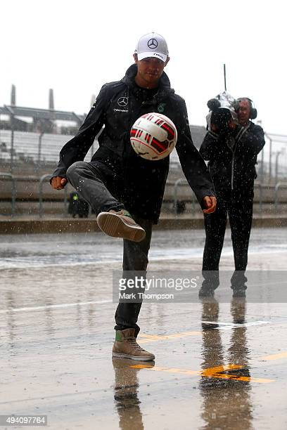 Nico Rosberg of Germany and Mercedes GP plays football in the pit lane as it rains after qualifying was suspended due to bad weather for the United...