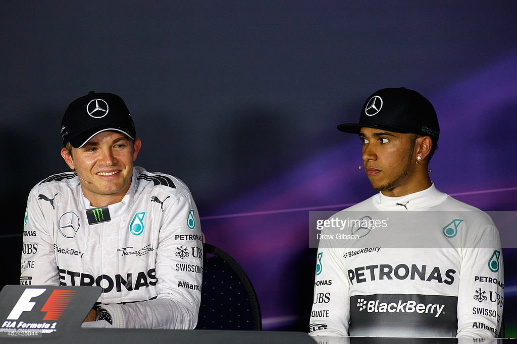 Nico Rosberg of Germany and Mercedes GP smiles next to Lewis Hamilton of Great Britain and Mercedes GP during the drivers' press conference after victory in the German Grand Prix at Hockenheimring on July 20, 2014 in Hockenheim, Germany.