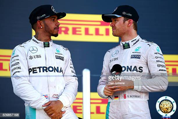 Nico Rosberg of Germany and Mercedes GP speaks with his teammate Lewis Hamilton of Great Britain and Mercedes GP as he celebrates his win on the...