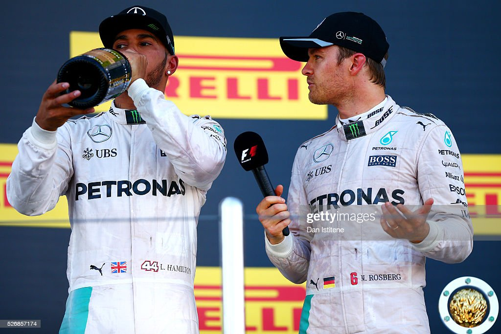 Nico Rosberg of Germany and Mercedes GP speaks with his team-mate Lewis Hamilton of Great Britain and Mercedes GP as he celebrates his win on the podium during the Formula One Grand Prix of Russia at Sochi Autodrom on May 1, 2016 in Sochi, Russia.