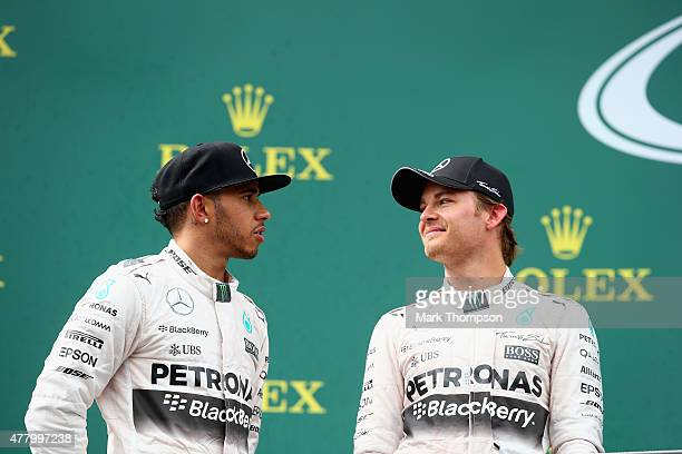 Nico Rosberg of Germany and Mercedes GP speaks with Lewis Hamilton of Great Britain and Mercedes GP on the podium after winning the Formula One Grand...