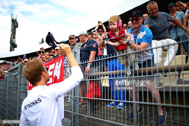 Nico Rosberg of Germany and Mercedes GP throws a cap to the fans during the drivers' parade before the Formula One Grand Prix of Germany at...