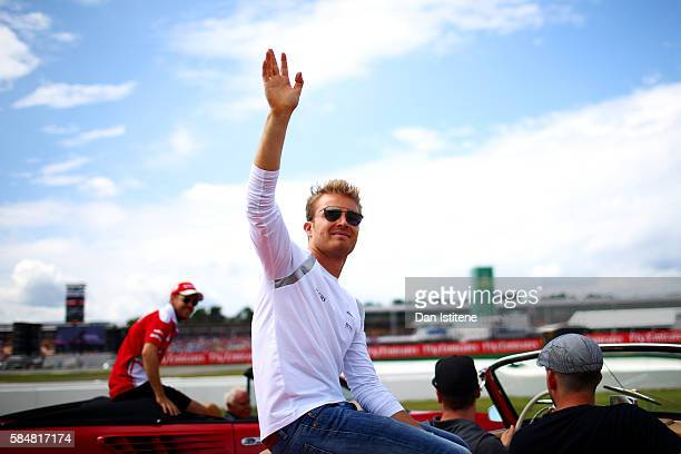 Nico Rosberg of Germany and Mercedes GP waves to the fans next to Sebastian Vettel of Germany and Ferrari during the drivers' parade before the...