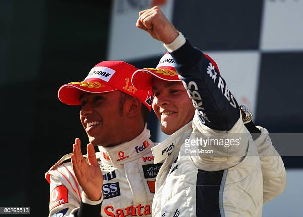 Nico Rosberg of Germany and Williams celebrates with race winner Lewis Hamilton of Great Britain and McLaren Mercedes on the podium after finishing...