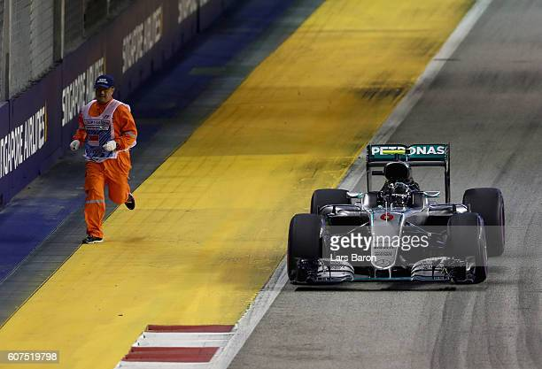 Nico Rosberg of Germany driving the Mercedes AMG Petronas F1 Team Mercedes F1 WO7 Mercedes PU106C Hybrid turbo past a marshal on track during the...