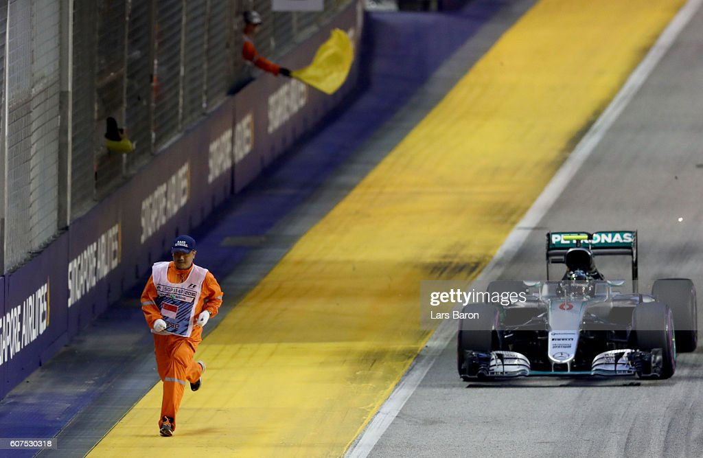 Nico Rosberg of Germany driving the (6) Mercedes AMG Petronas F1 Team Mercedes F1 WO7 Mercedes PU106C Hybrid turbo past a marshal on track during the Formula One Grand Prix of Singapore at Marina Bay Street Circuit on September 18, 2016 in Singapore.