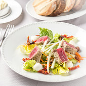 Nicoise salad with fresh vegetables and bread on table at restaurant