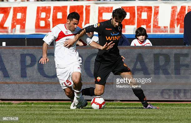 Nicola Belmonte of AS Bari battles for the ball with Mirko Vucinic of AS Roma during the Serie A match between AS Bari and AS Roma at Stadio San...