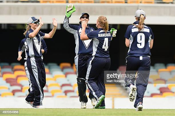 Nicola Hancock of the Spirit celebrates with team mates the wicket of Carly Ryan of the Roar during the round one WNCL match between Victoria and...