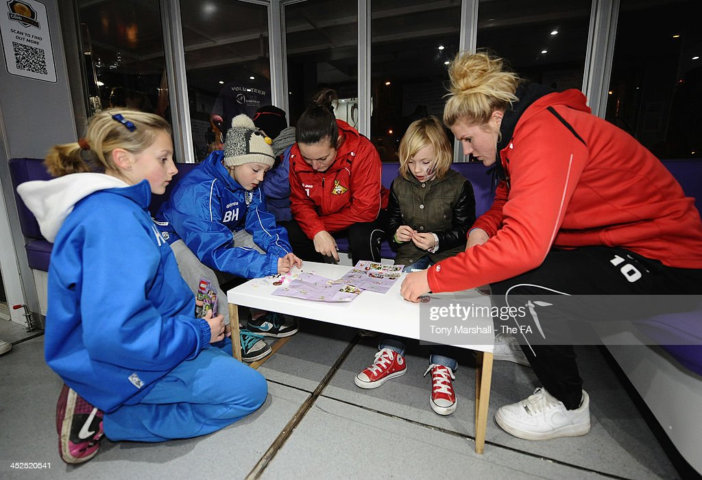 Nicola Hobbs and Millie Bright of Doncaster Rovers Belles help young fans making their Free Lego Toy at the FA Girls Fanzone before the UEFA Womens U17 Championship Finals match between England and Austria at Chesterfield FC Stadium on November 29, 2013 in Chesterfield, England.