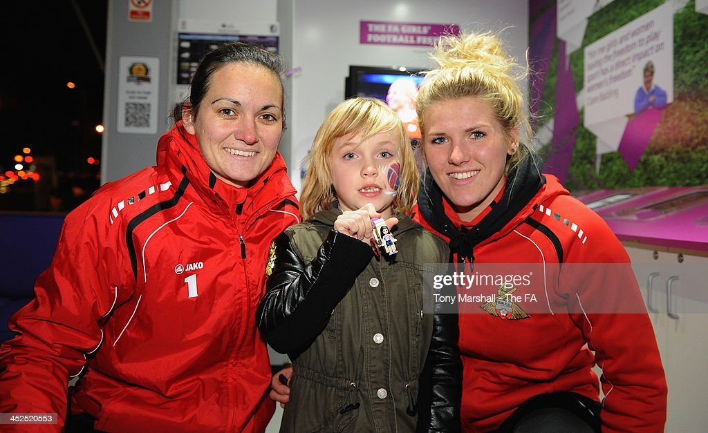 Nicola Hobbs and Millie Bright of Doncaster Rovers Belles with a young fan after assembling her Free Lego Toy at the FA Girls Fanzone before the UEFA Womens U17 Championship Finals match between England and Austria at Chesterfield FC Stadium on November 29, 2013 in Chesterfield, England.