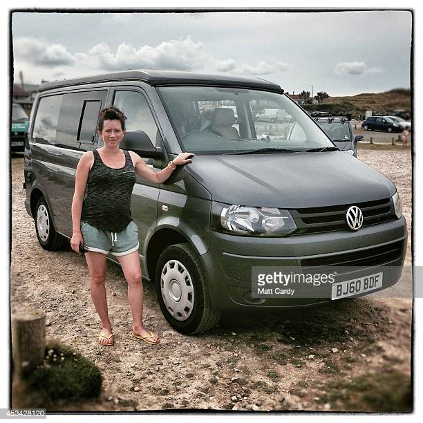 Nicola Rousseau from Surrey poses for a photograph besides her 2010 fifth generation T5 Volkswagen Transporter van near Newquay on August 8 2014 in...