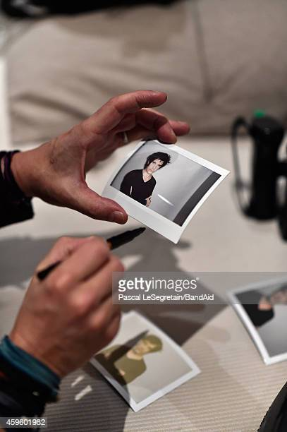 Nicola Sirkis sings an autograph on a polaroid during the Band Aid 30 'Noel est la' Recording on November 23 2014 in Paris France