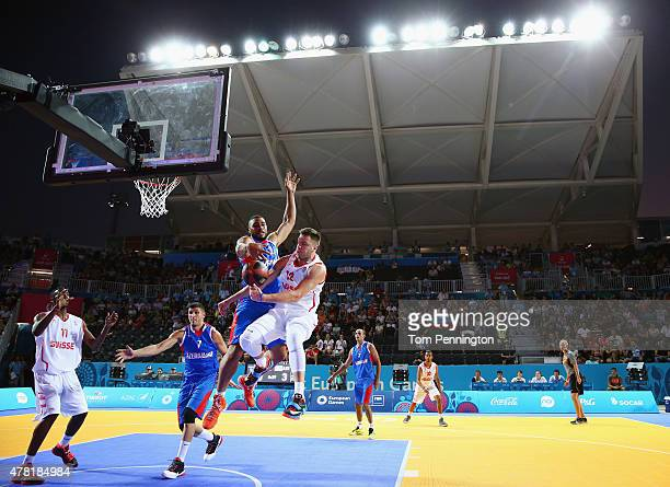 Nicola Stevanovic of Switzerland drives to the basket against Orhan Haciyeva of Azerbaijan and Marshall Obrain Moses during the Men's 3x3 Basketball...