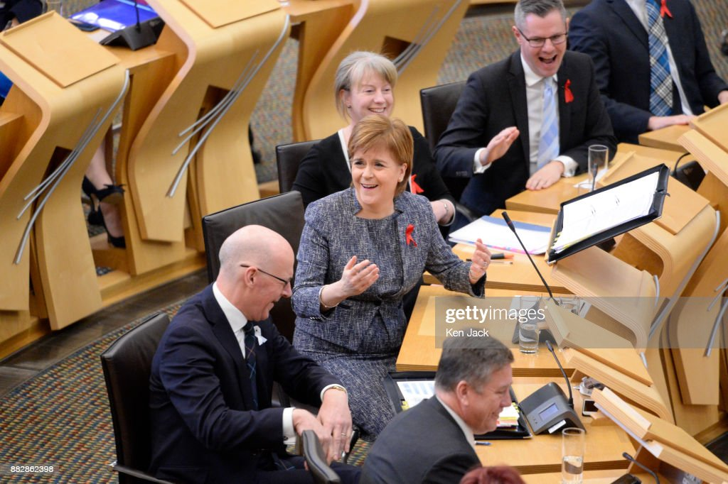 Nicola Sturgeon (C) and her front bench team react with hilarity during First Minister's Questions in the Scottish Parliament, on November 30, 2017 in Edinburgh, Scotland.