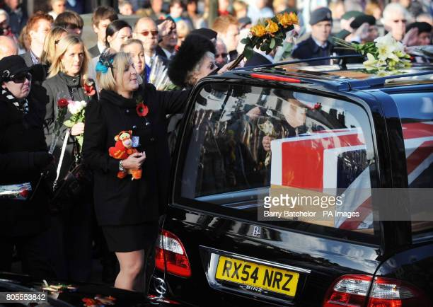 Nicola the wife of Corporal Loren MarltonThomas reaches forward to place flowers on a hearse as it carries the coffin of her husband through the...