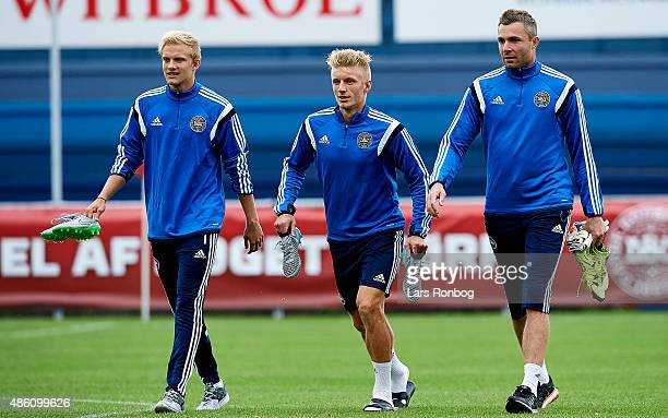 Nicolai Boilesen Daniel Wass and Goalkeeper Stephan Andersen walks on to the pitch prior to the Denmark training session at Helsingor Stadion on...