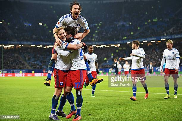 Nicolai Müller of Hamburg celebrates scoring his second goal with Albin Ekdal and Lewis Holtby during the Bundesliga match between Hamburger SV and...