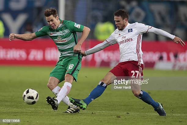 Nicolai Mueller of Hamburg and Niklas Moisander of Bremen compete for the ball during the Bundesliga match between Hamburger SV and Werder Bremen at...