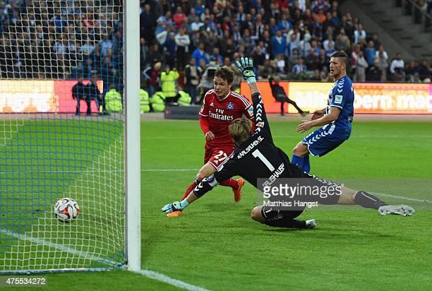 Nicolai Mueller of Hamburger SV beats goalkeeper Dirk Orlishausen of Karlsruher SC to score their second goal during the Bundesliga playoff second...