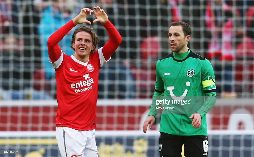 Nicolai Mueller of Mainz celebrates his team's first goal as he runs past Steven Cherundolo of Hannover during the Bundesliga match between 1 FSV...