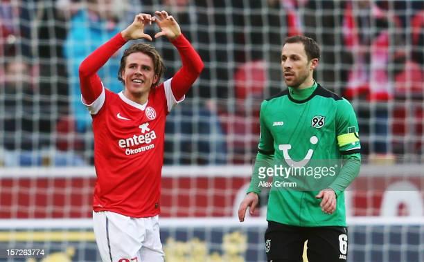 Nicolai Mueller of Mainz celebrates his team's first goal as he runs past Steven Cherundolo of Hannover during the Bundesliga match between 1 FSV...