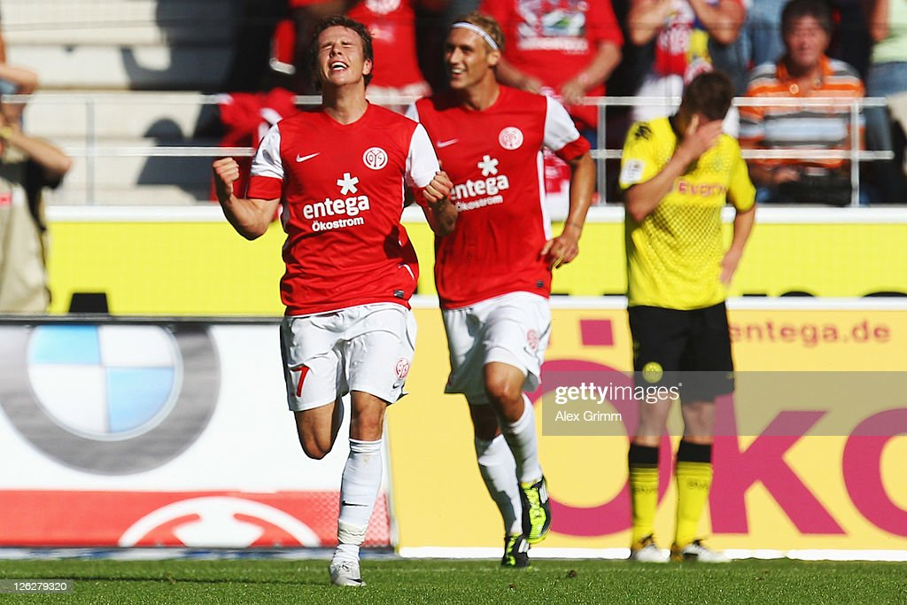 <a gi-track='captionPersonalityLinkClicked' href=/galleries/search?phrase=Nicolai+Mueller&family=editorial&specificpeople=2344337 ng-click='$event.stopPropagation()'>Nicolai Mueller</a> (L) of Mainz celebrates his team's first goal with team mate <a gi-track='captionPersonalityLinkClicked' href=/galleries/search?phrase=Marcel+Risse&family=editorial&specificpeople=4331527 ng-click='$event.stopPropagation()'>Marcel Risse</a> as <a gi-track='captionPersonalityLinkClicked' href=/galleries/search?phrase=Lukasz+Piszczek&family=editorial&specificpeople=4380352 ng-click='$event.stopPropagation()'>Lukasz Piszczek</a> of Dortmund reacts during the Bundesliga match between FSV Mainz 05 and Borussia Dortmund at Coface Arena on September 24, 2011 in Mainz, Germany.