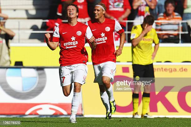 Nicolai Mueller of Mainz celebrates his team's first goal with team mate Marcel Risse as Lukasz Piszczek of Dortmund reacts during the Bundesliga...