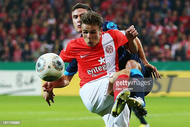 Nicolai Mueller of Mainz is challenged by Jonas Hector of Koeln during the DFB Cup second round match between 1 FSV Mainz 05 and 1 FC Koeln at Coface...