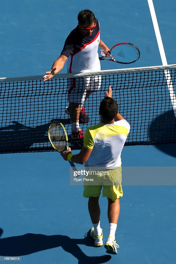 Nicolas Almagro of Spain and Janko Tipsarevic of Serbia shake hands at the net after Tipsarevic retired from their fourth round match during day seven of the 2013 Australian Open at Melbourne Park on January 20, 2013 in Melbourne, Australia.