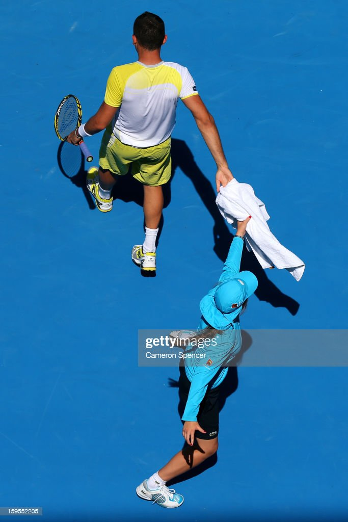 Nicolas Almagro of Spain hands a towel to a ball boy in his second round match against Daniel GimenoTraver of Spain during day three of the 2013...