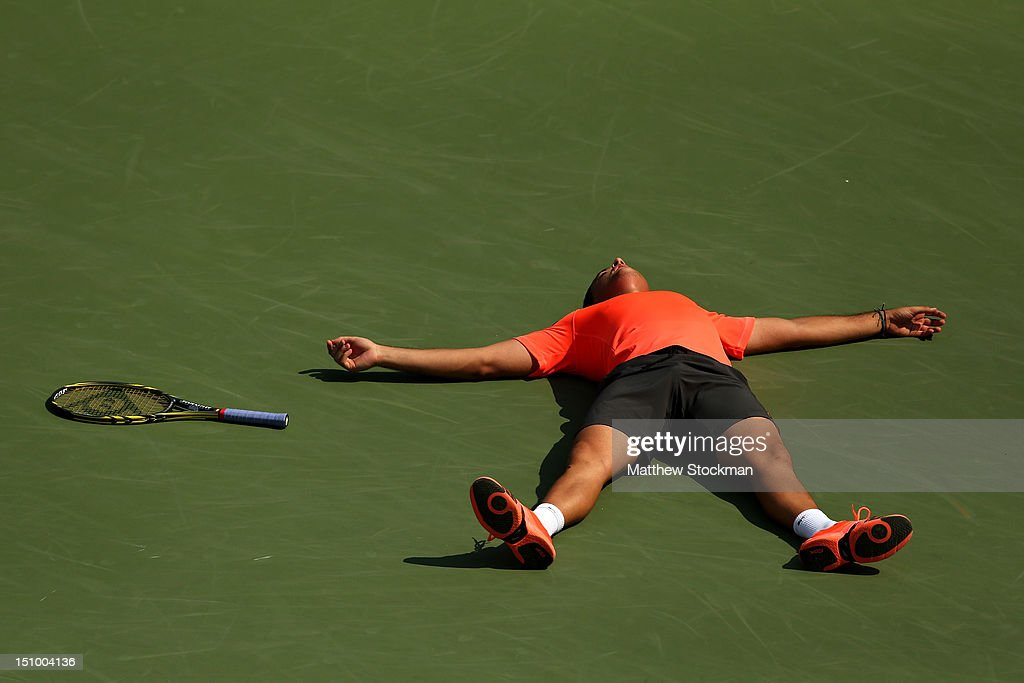 Nicolas Almagro of Spain lies on the court as he celebrates match point after his men's singles second round match against Philipp Petzschner of Germany during Day Four of the 2012 US Open at USTA Billie Jean King National Tennis Center on August 30, 2012 in the Flushing neigborhood of the Queens borough of New York City.