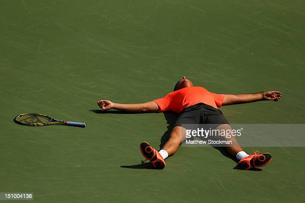 Nicolas Almagro of Spain lies on the court as he celebrates match point after his men's singles second round match against Philipp Petzschner of...