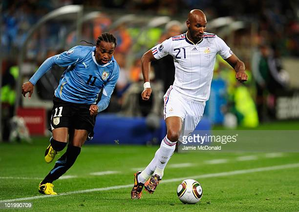 Nicolas Anelka of France sprints with the ball from Alvaro Pereira of Uruguay during the 2010 FIFA World Cup South Africa Group A match between...