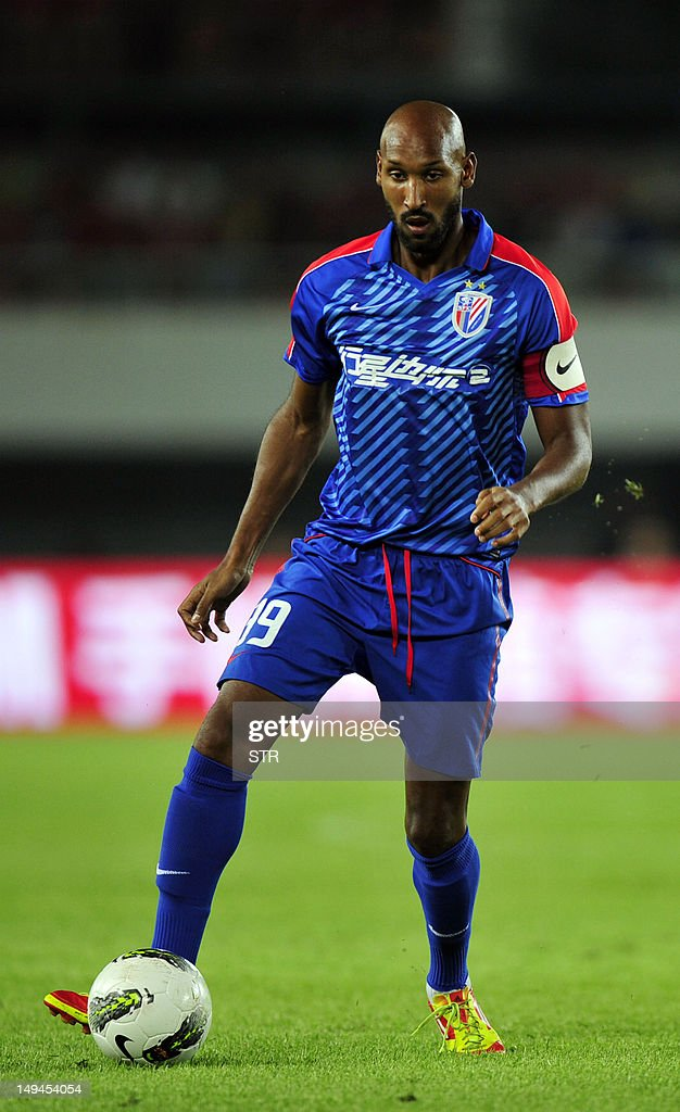 Nicolas Anelka of Shanghai Shenhua dribbles the ball against Guangzhou Evergrande in a Chinese Super League football match in Guangzhou, southern China's Guangdong province on July 28, 2012. Didier Drogba lead his new team Shanghai Shenhua to a 2-2 draw against league leader Guangzhou Evergrande, managed by Italian World-Cup winning coach Marcello Lippi. CHINA OUT AFP PHOTO