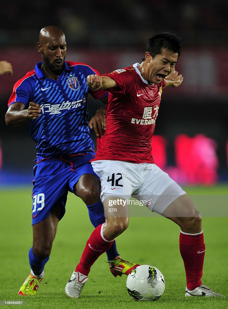 Nicolas Anelka of Shanghai Shenhua (L) fights for the ball against Huang Bowen (R) of Guangzhou Evergrande in a Chinese Super League football match in Guangzhou, southern China's Guangdong province on July 28, 2012. Didier Drogba lead his new team Shanghai Shenhua to a 2-2 draw against league leader Guangzhou Evergrande, managed by Italian World-Cup winning coach Marcello Lippi. CHINA OUT AFP PHOTO