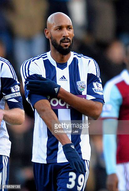 Nicolas Anelka of West Brom touches his sleeve as he celebrates scoring their first goal during the Barclays Premier League match between West Ham...
