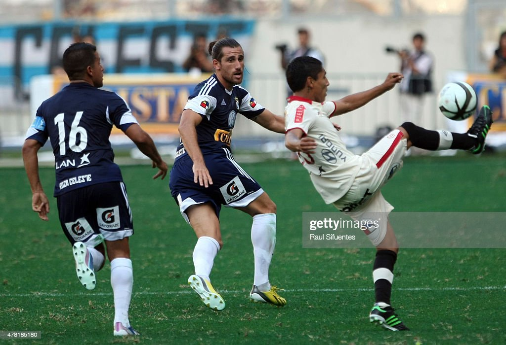 Nicolas Ayr (C) of Sporting Cristal fights for the ball with Raul Ruidiaz (R) of Universitario during a match between Sporting Cristal and Universitario as part of the Torneo Descentralizado 2013 at the National Stadium on April 28, 2013 in Lima, Peru