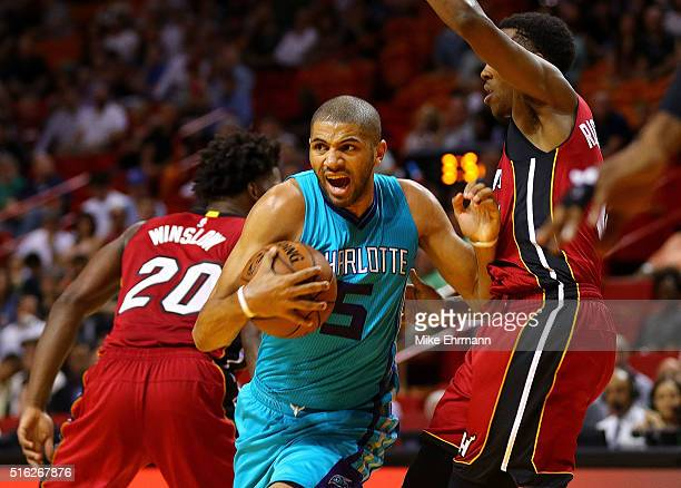 Nicolas Batum of the Charlotte Hornets drives on Josh Richardson of the Miami Heat during a game at American Airlines Arena on March 17 2016 in Miami...
