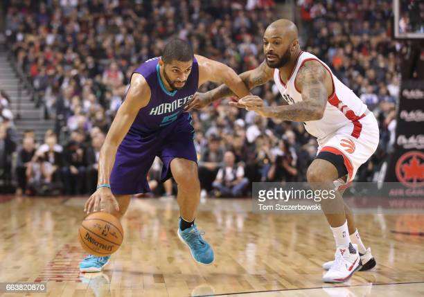 Nicolas Batum of the Charlotte Hornets goes to the basket against PJ Tucker of the Toronto Raptors during NBA game action at Air Canada Centre on...