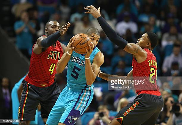 Nicolas Batum of the Charlotte Hornets is trapped by teammates Paul Millsap and Kent Bazemore of the Atlanta Hawks during their game at Time Warner...