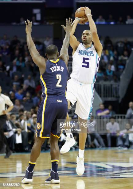Nicolas Batum of the Charlotte Hornets shoots over Rodney Stuckey of the Indiana Pacers during their game at Spectrum Center on March 6 2017 in...