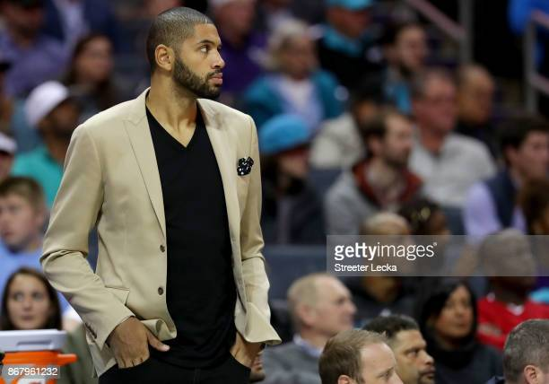 Nicolas Batum of the Charlotte Hornets watches on from the bench against the Orlando Magic during their game at Spectrum Center on October 29 2017 in...