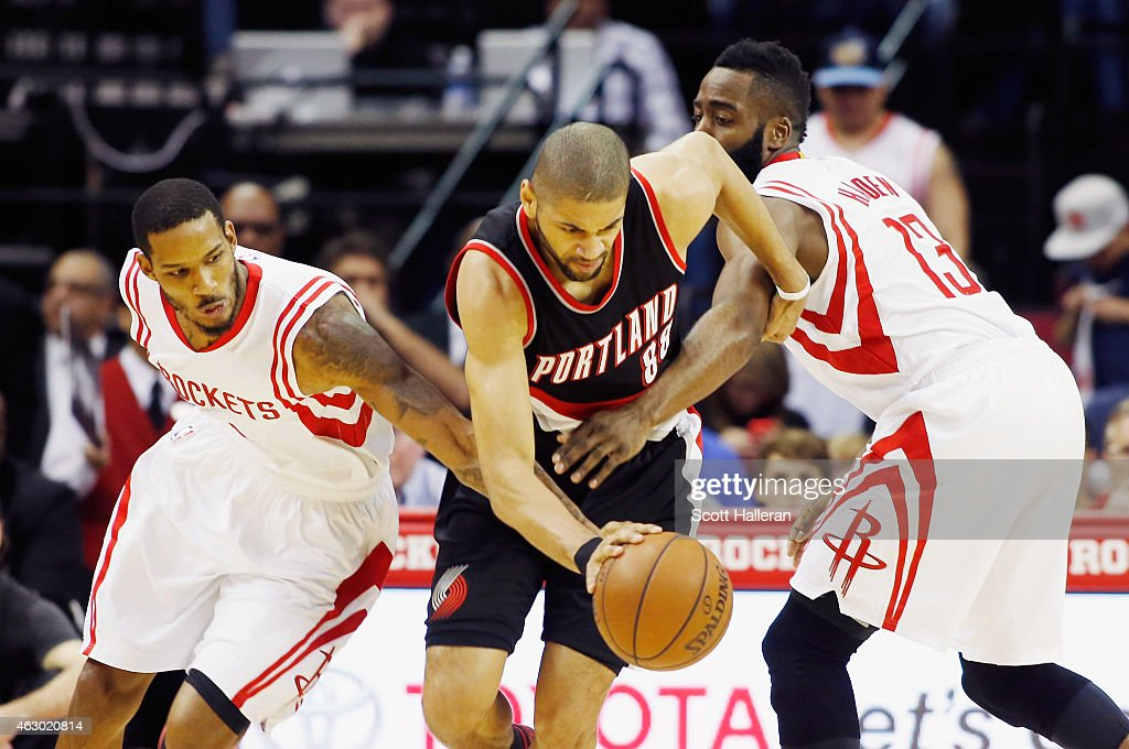 <a gi-track='captionPersonalityLinkClicked' href=/galleries/search?phrase=Nicolas+Batum&family=editorial&specificpeople=3746275 ng-click='$event.stopPropagation()'>Nicolas Batum</a> #88 of the Portland Trail Blazers drives with the ball against <a gi-track='captionPersonalityLinkClicked' href=/galleries/search?phrase=Trevor+Ariza&family=editorial&specificpeople=201708 ng-click='$event.stopPropagation()'>Trevor Ariza</a> #1 and <a gi-track='captionPersonalityLinkClicked' href=/galleries/search?phrase=James+Harden&family=editorial&specificpeople=4215938 ng-click='$event.stopPropagation()'>James Harden</a> #13 of the Houston Rockets during their game at the Toyota Center on February 8, 2015 in Houston, Texas.