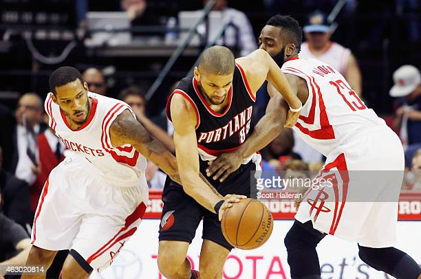 Nicolas Batum of the Portland Trail Blazers drives with the ball against Trevor Ariza and James Harden of the Houston Rockets during their game at...