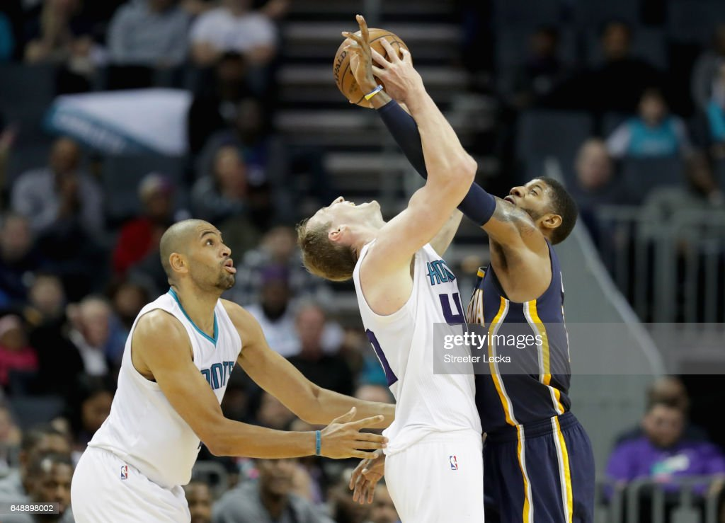 Nicolas Batum #5 watches as teammate Cody Zeller #40 of the Charlotte Hornets battles for the ball against Paul George #13 of the Indiana Pacers during their game at Spectrum Center on March 6, 2017 in Charlotte, North Carolina.