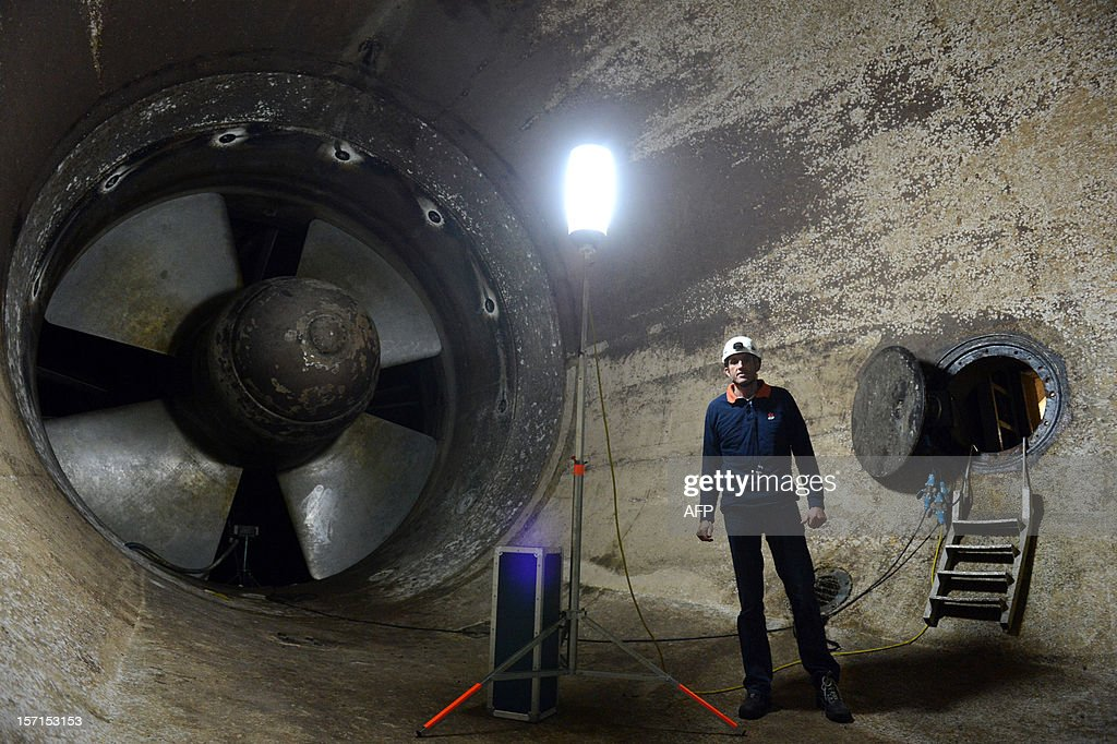 Nicolas Bec, an employee in charge of the site, poses in front of one of the 24 turbines of the La Rance tidal-turbine power plant on November 28, 2012 in La Richardais, western France.