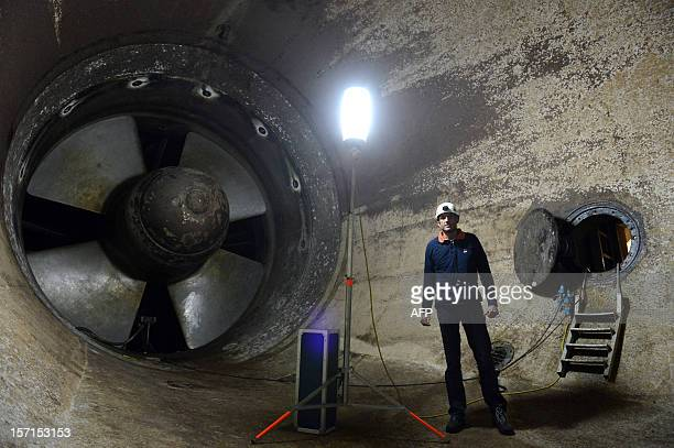 Nicolas Bec an employee in charge of the site poses in front of one of the 24 turbines of the La Rance tidalturbine power plant on November 28 2012...