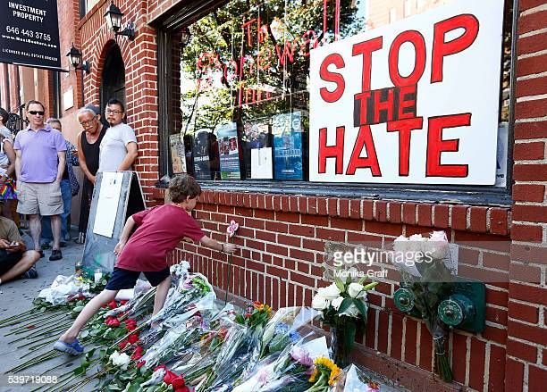 Nicolas BrownSpino sets down a paper flower at a makeshift memorial in front of the Stonewall Inn as people gather for a vigil following the massacre...